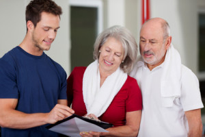 Instructor Showing Health Results On Clipboard To Senior Couple