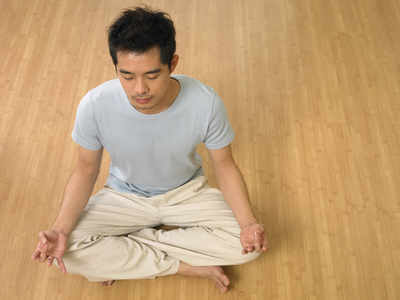 man doing yoga at home with eye closed