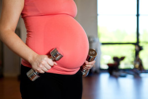 Pregnant woman holding dumbbells