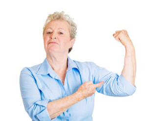Closeup portrait of smiling senior mature woman flexing muscles showing displaying her gun show, isolated on white background. Positive emotion facial expression feelings, attitude, perception