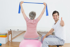 Physical therapist gesturing thumbs up besides senior woman on yoga ball