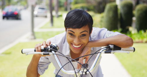 Black woman ringing bicycle bell and smiling outdoors