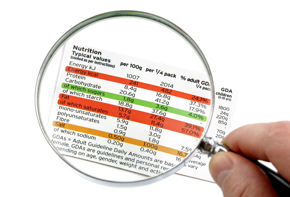 Reading a nutrition label on food packaging with magnifying glass