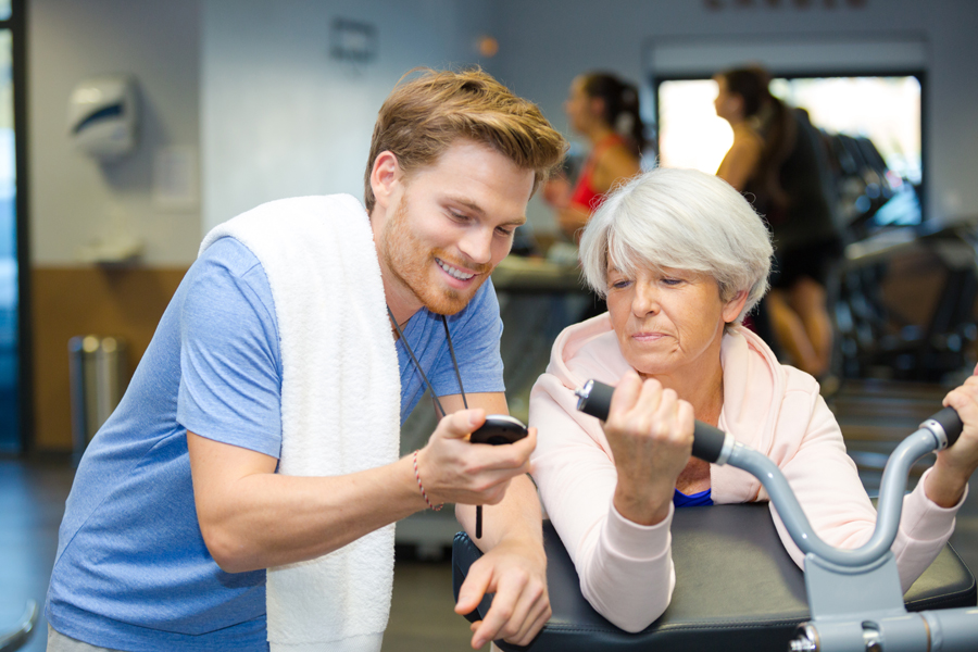 personal trainer showing stopwatch time to senior client