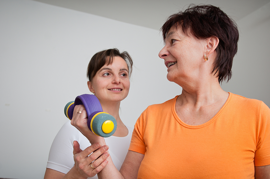 Senior woman exercising with trainer