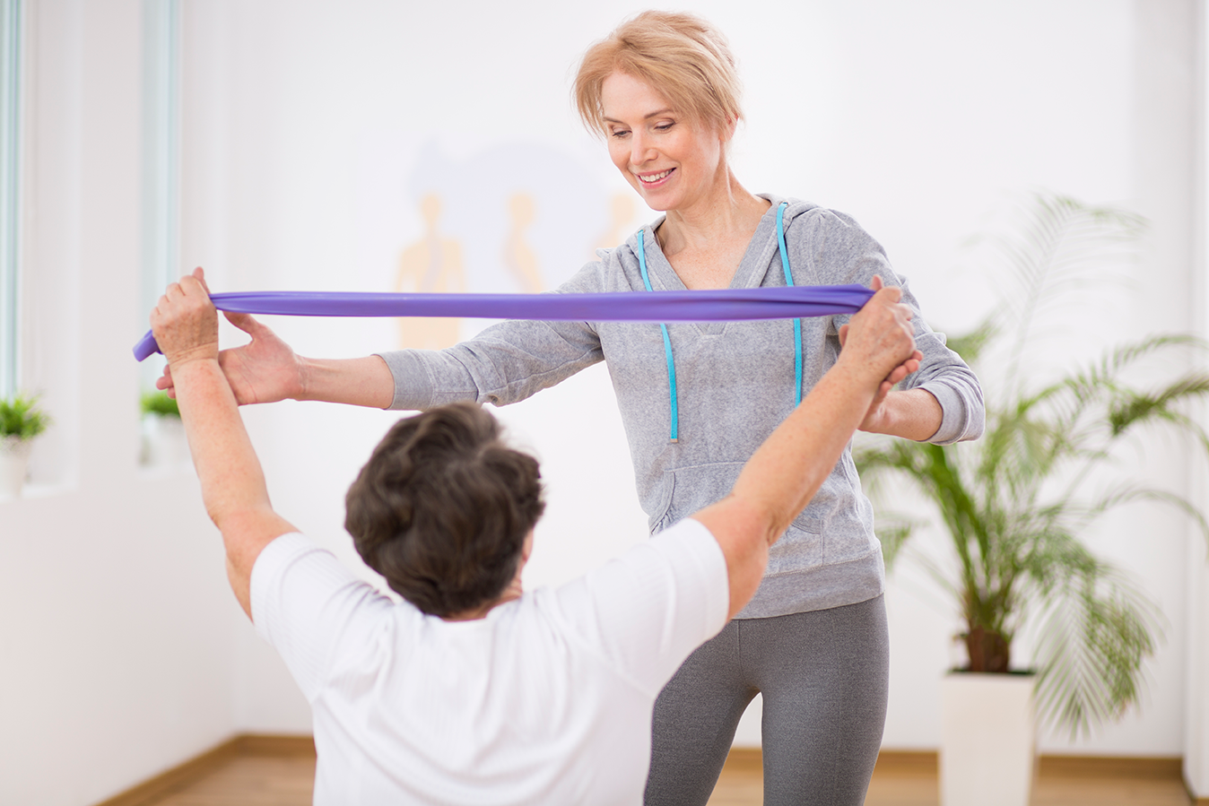 trainer-resistance-band-senior-woman-client