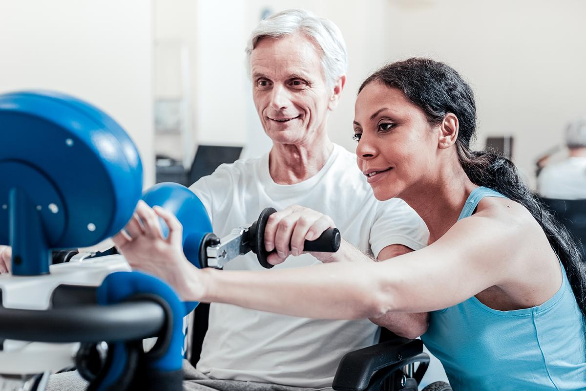 Trainer-with-senior-client-using-machine