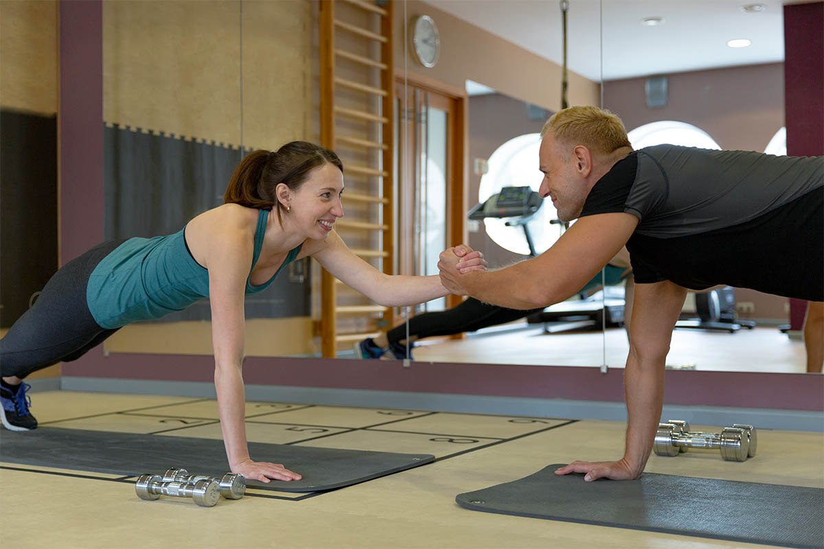 Fitness parners in sportswear doing exercises at gym. Fitness sp