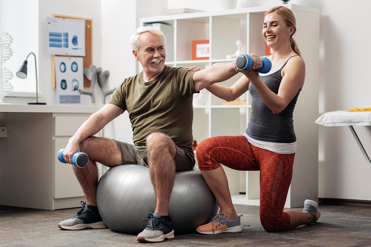 female-trainer-senior-client-exercise-ball